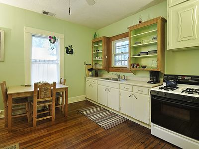 Kitchen with gas stove, plenty of nice, matching plates, silverware.