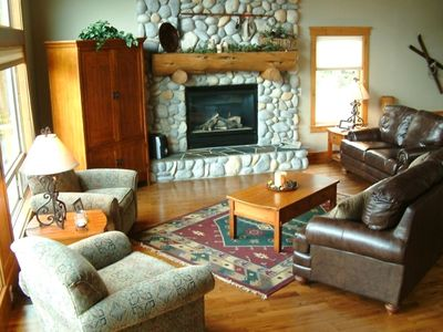 Great Room is spacious with a river rock fireplace creating a cozy atmosphere
