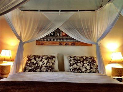 King bed with mosquito netting canopy and tapa cloth art.