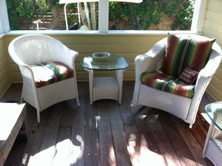 Screened porch with beautiful, comfortable wicker love seat, rocker and 2 chairs