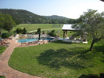 View of pool & hot tub with pavilion from veranda of main house
