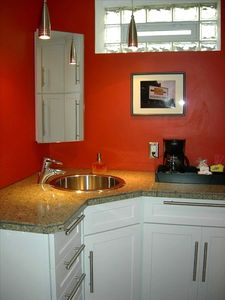Bathroom with Cambria countertops, ample cabinetry, hair dryer, opening window.