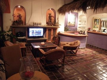 TV Viewing in comfortable leather chairs, bar, nichos with pre-columbian Art