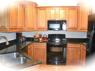 Private Homes house photo - Kitchen with stove, microwave, refrigerator w, ice maker, and coffee maker...