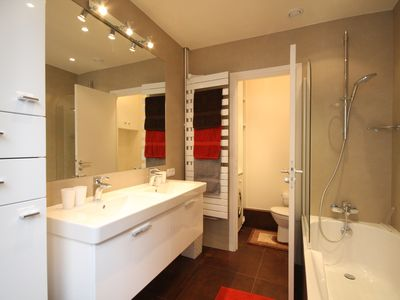 Stylish bathroom with double wash basins and separate WC/laundry