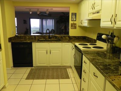 New granite countertops in this spacious, fully equipped kitchen.