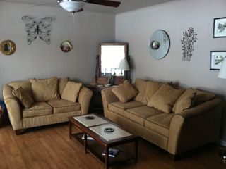 Couch and love seat in the living room. A large picture window with a lakeview.