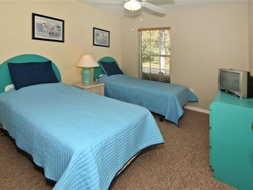 Bedroom Four with twin beds, ceiling fan and TV.