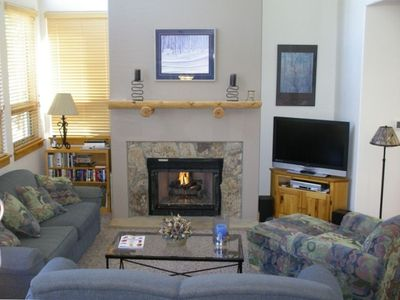 Living Room with Fireplace, large flat screen TV and comfortable seating area.