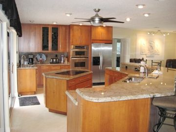 Cherry and granite stainless steel applianced kitchen with stools