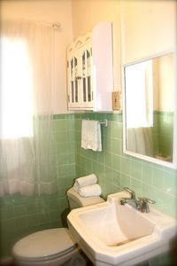 Bathroom with clear glass tiled floor, all linens and paper products included.