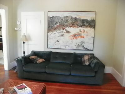 Spacious living area includes large,comfy sofa, original artwork of river rafter