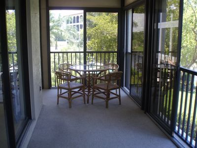 another view of lanai, this showing wicker furniture and round topped table