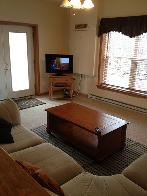 Sectional couch with flatscreen , DVD , on lower floor area.