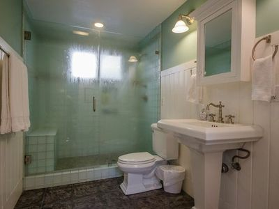 Spacious Bathrooms with glass shower enclosures are attached to each room