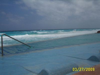 Sunbath while lying in the pool water. Pool is level with the ocean wall.
