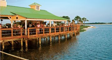 Walk out the Pier to Limes Bar and Grill. Great food and atmosphere !