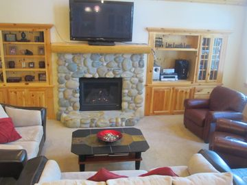 Family room with stone fireplace, a large flat screen TV and comfortable seating