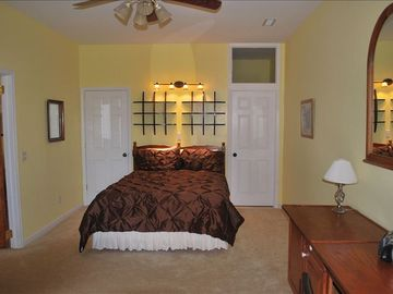 Queen bed with grand view of spacious bedroom and windows looking at mountains