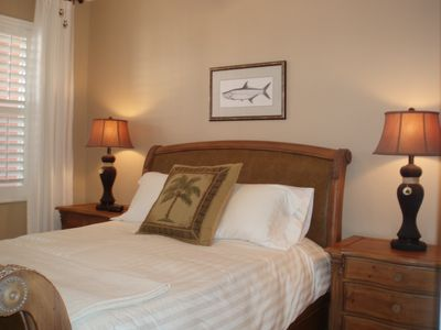 Queen-sized bed and beautiful art in guest bedroom!