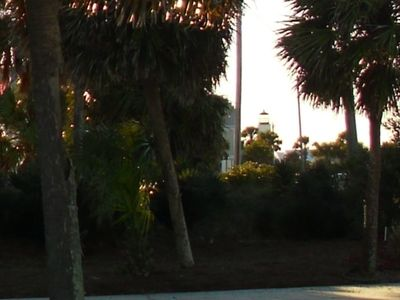 Lighthouse among palms as viewed from parking lot of home.