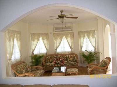 View of livingroom with delightful tropical furnitue, ceiling fan, and AC unit