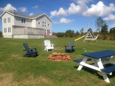 Angie's Beach House has a beautiful back yard with fire pit, hot tub & playset.