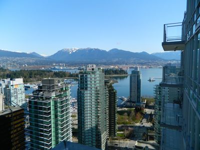Balcony view of snow-capped mountains and Stanley Park