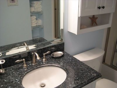 Modern Bathroom with Granite Vanity and Cultured Marble Shower Surround.