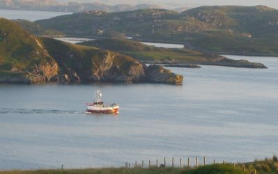 A trawler in the setting sun below The Brochs