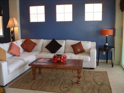 Living area has large L-shaped sofa, teak coffee table and area carpet.