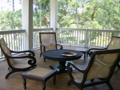 Comfortable seating on covered deck overlooking scenic views and pool