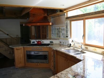 Gourmet kitchen with a pizza oven, a commercial cook top, and dishwasher.
