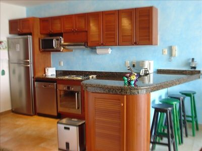 Modern kitchen features a granite counter top and full size appliances.