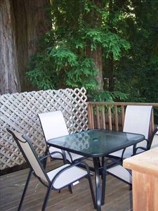 Table and chairs on the deck under the Redwood Trees overlooking the river.