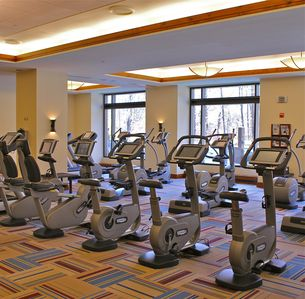 Spacious fitness center overlooking outdoor pools