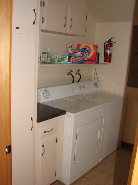 Fully equipped laundry room with heavy-duty WD; iron and ironing board