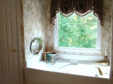 Jacuzzi bathtub for two with custom made drapery overlooking private backyard.