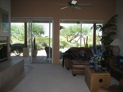 Great room, with windows that look out to patio and desert. Leather furniture