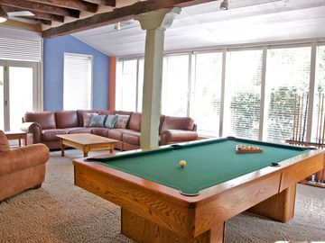 Den with pool table and piano.