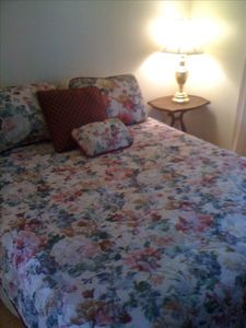 Queen sized bed. Romantic roses on comforter and paintings.