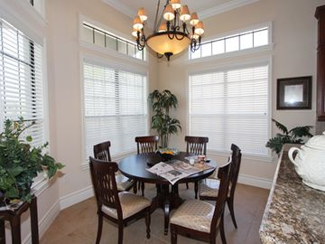 The breakfast dining area with bay windows that overlook the pool
