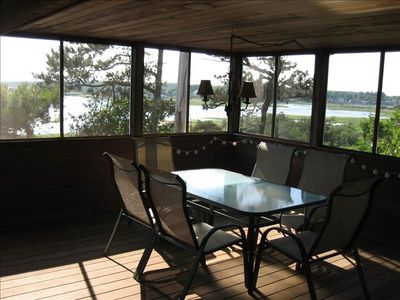 Screened Porch with dining table and oversized chairs with views of the harbor