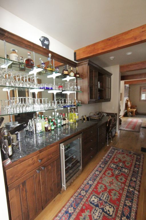 Fully outfitted bar with glassware and beverage and wine cooler