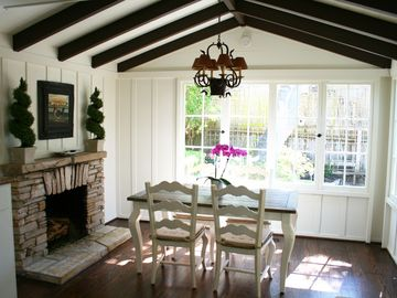 Carmel cottage rental - Eating area opens to kitchen with gas fireplace and surrounded by windows