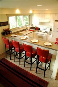 Fully appointed kitchen with breakfast bar & red leather bar stools
