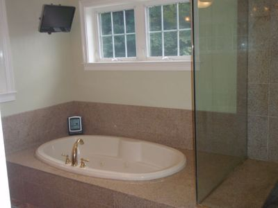 Master bath jacuzzi tub, shower with multi-head sprayers, and 2 shower heads