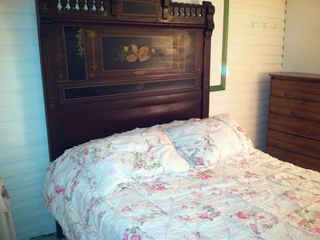 Full size bed with pink flowery bedspread