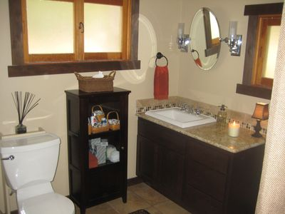 Bathroom with large walk-in shower and washer/dryer.