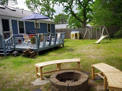 Wood deck with 2 Weber BBQs overlooks fenced back yard w/ fire pit & swing set.